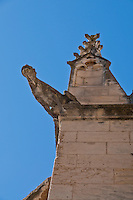 Stone animal grotesque against a blue sky at an ancient church in Arles, France.