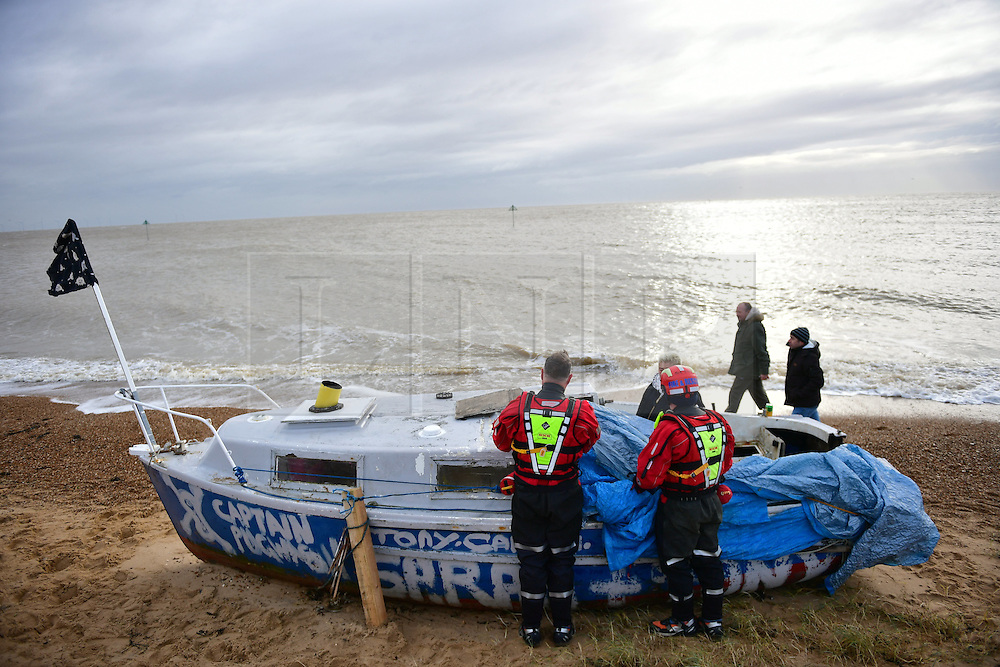 © Licensed to London News Pictures. 13/01/2017. Jaywick, UK. Members of a search and rescue team inspect a boat on the seafront at Jaywick before Homes are evacuated due to the threat of flooding in low-lying areas . Photo credit: Ben Cawthra/LNP