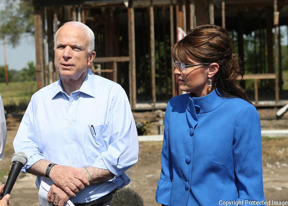 US Republican presidential nominee Senator John McCain (R-AZ) and his running mate Alaska Govenor Sarah Palin address the media outside a flood damaged house after a campaign rally in Cedar Rapids, Iowa, September 18, 2008.