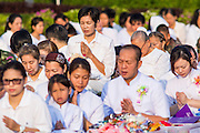 20 OCTOBER 2012 - BANGKOK, THAILAND:  Members of the public pray for peace in southern Thailand during a special alms giving ceremony in Bangkok. More than 2,600 Buddhist Monks from across Bangkok and thousands of devout Thai Buddhists attended the mass alms giving ceremony in Benjasiri Park in Bangkok Saturday morning. The ceremony was to raise food and cash donations for Buddhist temples in Thailand's violence plagued southern provinces. Because of an ongoing long running insurgency by Muslim separatists many Buddhist monks in Pattani, Narathiwat and Yala, Thailand's three Muslim majority provinces, can't leave their temples without military escorts. Monks have been targeted by Muslim extremists because, in the view of the extremists, they represent the Thai state.       PHOTO BY JACK KURTZ