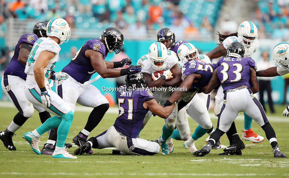 Miami Dolphins running back Lamar Miller (26) gets gang tackled by Baltimore Ravens inside linebacker Daryl Smith (51) and Baltimore Ravens outside linebacker Elvis Dumervil (58) as he runs the ball up the middle during the 2015 week 13 regular season NFL football game against the Baltimore Ravens on Sunday, Dec. 6, 2015 in Miami Gardens, Fla. The Dolphins won the game 15-13. (©Paul Anthony Spinelli)