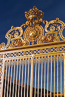 The ornate golden entrance gates to the Chateau Versaille on the outskirts of Paris, France