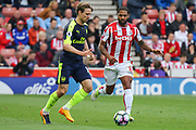 Arsenal defender Nacho Monreal and  Stoke City defender Glen Johnson challenge for the ball during the Premier League match between Stoke City and Arsenal at the Bet365 Stadium, Stoke-on-Trent, England on 13 May 2017. Photo by Aaron  Lupton.