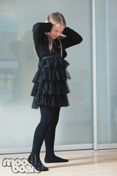 Frustrated young girl in black clothing covering ears