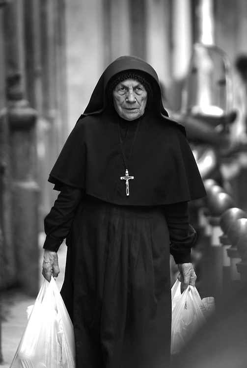 Black and white photograph of nun with shopping bags in Bologna Italy.