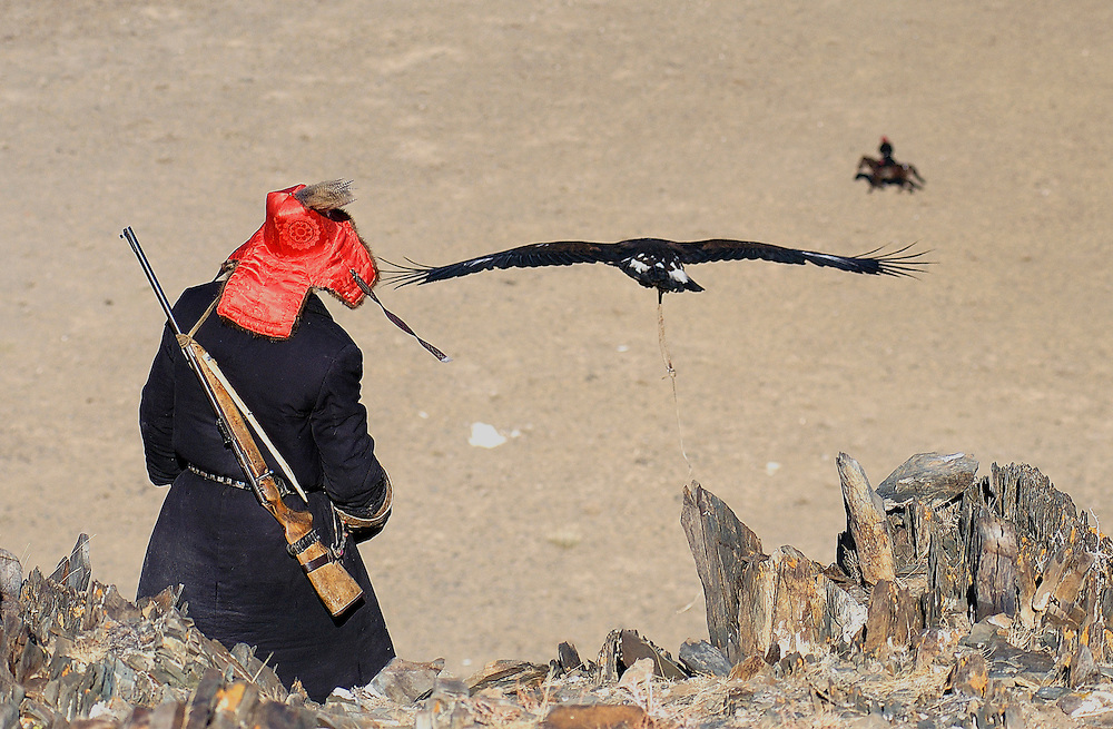 An eagle hunter releases a golden eagle flying to another eagle hunter in the valley below at the annual eagle hunting festival.