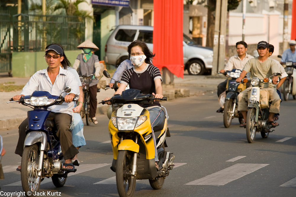 08 MARCH 2006 - HO CHI MINH CITY, VIETNAM: Motorcycle traffic in Ho Chi Minh City, Vietnam. HCMC is still widely known as Saigon. Many people wear face masks because of the air pollution in Ho Chi Minh City. PHOTO BY JACK KURTZ