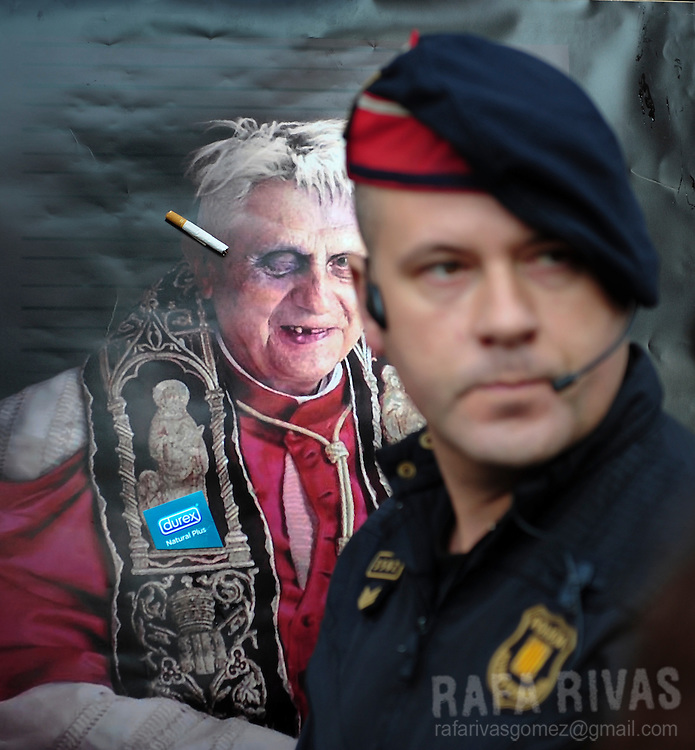 A Cataluna regional police member, Mosso D'esquadra, stands in front of a portrait of the Pope during a demonstration against Pope Benedict XVI's visit, on november 6, 2010, in Barcelona. Benedict XVI will visit Barcelona on November 7 where he will be consecrating Barcelona famous temple, the Sagarada Famila church. Photo Rafa Rivas