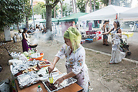 "ROME, ITALY - 3 JULY 2016: Gipsy Queen member Codruta Balteau (24, center) prepares typical Roma dishes at their food stand at the iFest, an alternative music festival  in Rome, Italy, on July 3rd 2016.<br /> <br /> The Gipsy Queens are a travelling catering business founded by Roma women in Rome.<br /> <br /> In 2015 Arci Solidarietà, an independent association for the promotion of social development, launched the ""Tavolo delle donne rom"" (Round table of Roma women) to both incentivise the process of integration of Roma in the city of Rome and to strengthen the Roma women's self-esteem in the context of a culture tied to patriarchal models. The ""Gipsy Queens"" project was founded by ten Roma women in July 2015 after an event organised together with Arci Solidarietà in the Candoni Roma camp in the Magliana, a neighbourhood in the South-West periphery of Rome, during which people were invited to dance and eat Roma cuisine. The goal of the Gipsy Queen travelling catering business is to support equal opportunities and female entrepreneurship among Roma women, who are often relegated to the roles of wives and mothers."