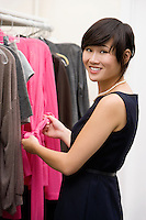 Happy fashion designer standing by clothing rack at store