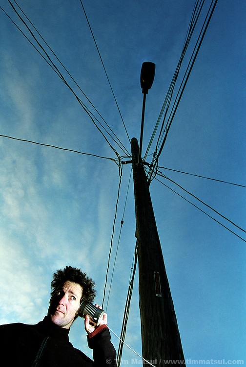 A caucasian man uses a tin can and string telephone near a telephone pole.