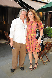 """MARTIN MILLER and his wife IOANA at a party to celebrate the publication of the Paper back edition of """"A Lion Called Christian"""" held at Julie's Restaurant & Bar, 135 Portland Road, London W11 on 28th June 2010."""