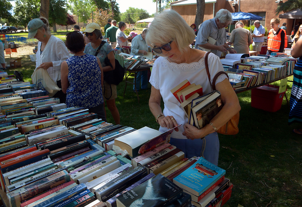 gbs060417a/RIO-WEST -- Wanda Barrows of Corrales peruses through books at the Friends of Corrales Library Spring Book Sale in La Entrada Park by the library on Sunday, June 4, 2017. Thousands of books, most priced at $2 for hardback and $1 for paperback were for sale.Proceeds form the sale support the Corrales Community Library.(Greg Sorber/Albuquerque Journal)