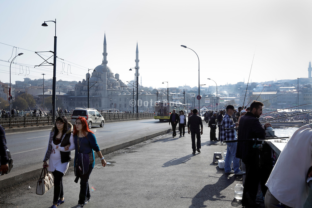 on the Galata Bridge in Istanbul Turkey with the Yeni Camii in the background