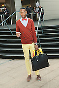 An man leaves the Mercedes-Benz New York Fall Fashion Week show wearing a red bow tie in honor of Valentine's Day.