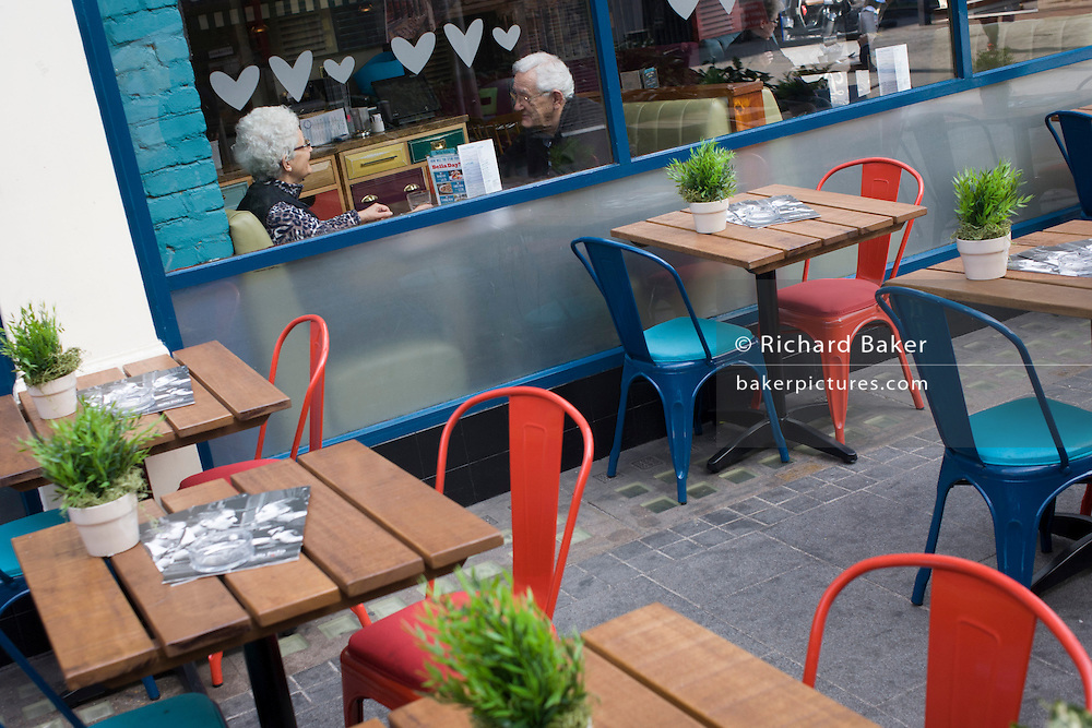 An elderly couple sit in a central London cafe window with love hearts theme stencils