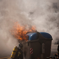 A large plastic garbage container burns as a fire fighter tries to put it out.