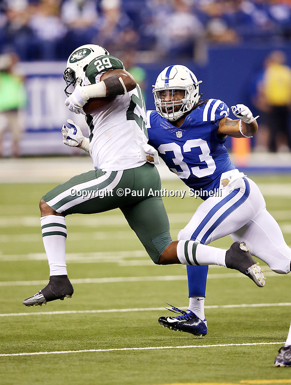 New York Jets running back Bilal Powell (29) leaps as he runs the ball and burns the clock in the fourth quarter while being chased by Indianapolis Colts free safety Dwight Lowery (33) during the 2015 NFL week 2 regular season football game against the Indianapolis Colts on Monday, Sept. 21, 2015 in Indianapolis. The Jets won the game 20-7. (©Paul Anthony Spinelli)