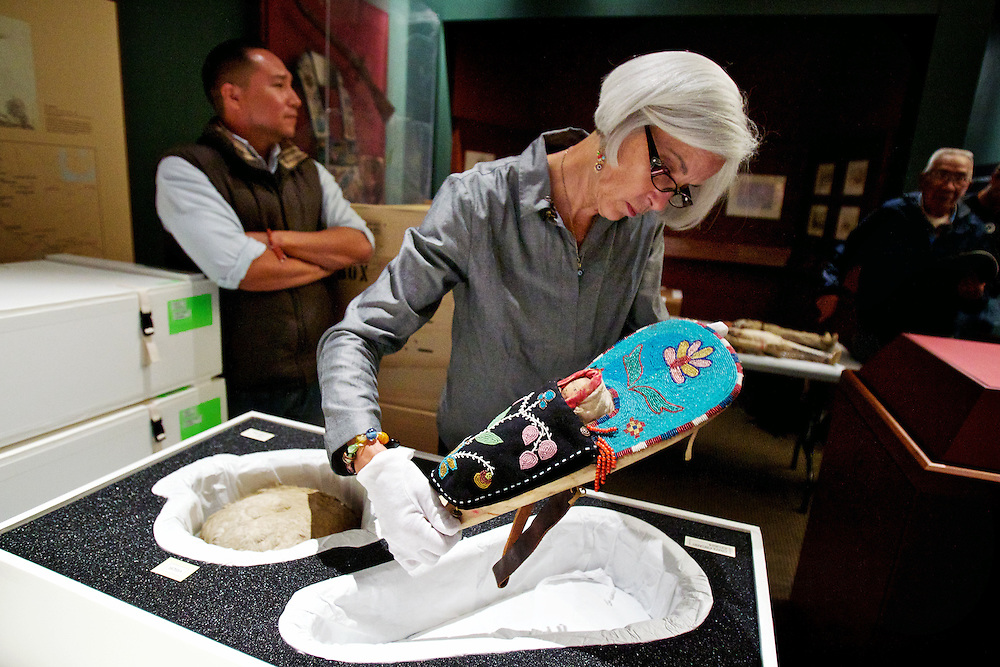 Greta Hansen, the conservator for the department of anthropology at the Smithsonian Museum of Natural History, carefully removes a handmade doll from a storage box Thursday at the Old Mission State Park museum in Cataldo. A total of three dolls that were crafted more than 100 years ago by Coeur d'Alene tribal members will be on display in the Sacred Encounters Exhibit that opens Oct. 15.
