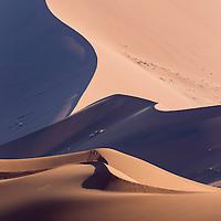 Africa, Namibia, Namib Naukluft National Park, Morning sun lights windblown red sand dunes in Namib Desert near Sossusvlei