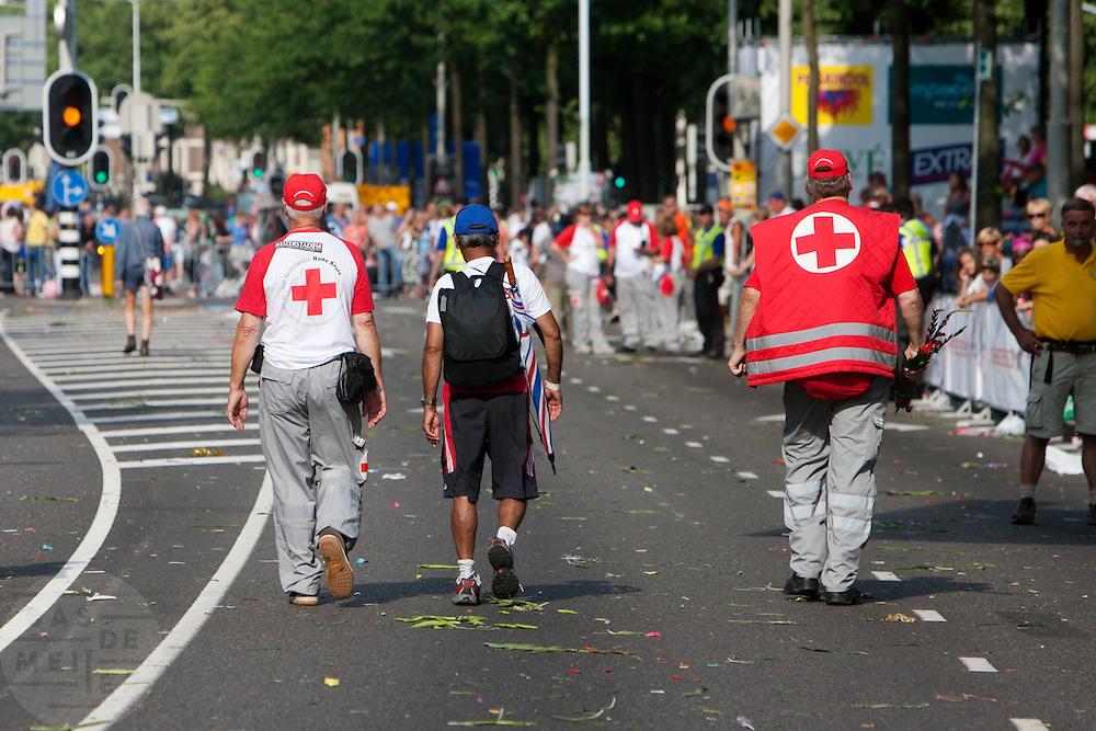 Onder begeleiding van medewerkers van het Rode Kruis legt de laatste loper van de Nijmeegse Vierdaagse zijn laatste meters af op de Via Gladiola. Lopers na hem zullen niet op tijd finishen.