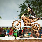 Long shot shows motocross racer seated on motorcycle while executing a single jump and waving to the audience in Belmopan, Belize.
