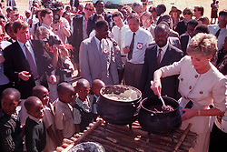 "Embargoed to 0001 Monday August 21 File photo dated 12/07/93 of children wait in line as Diana, Princes of Wales lends a hand to serve the food at the Child Feeding Scheme at Nemazuva Primary School in Zimbabwe. Diana, Princess of Wales was a woman whose warmth, compassion and empathy for those she met earned her the description the ""people's princess""."