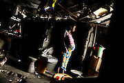 Marbella Slum, Freetown, Sierra Leone: Kadiazu (age unknown, probably under 20) stands in before her home. She does not know how far along she is in her third pregnancy. Both of her babies died within months of their birth. Kadiazu will deliver at home as she did in the two pregnancies before. She lives about 200 metres from the nearest health centre but has never been there in her life - although health care for pregnant mothers and children under 5 years of age is free since some months in Sierra Leone.