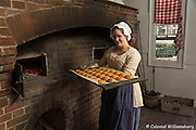 DOWNLOADABLE <br /> The Raleigh Tavern Bakery making gingerbread cookies for sale. Bakery staff Colleen Wempler (glasses and striped top and apron) with a tray of cookies right out of the wood fired oven.