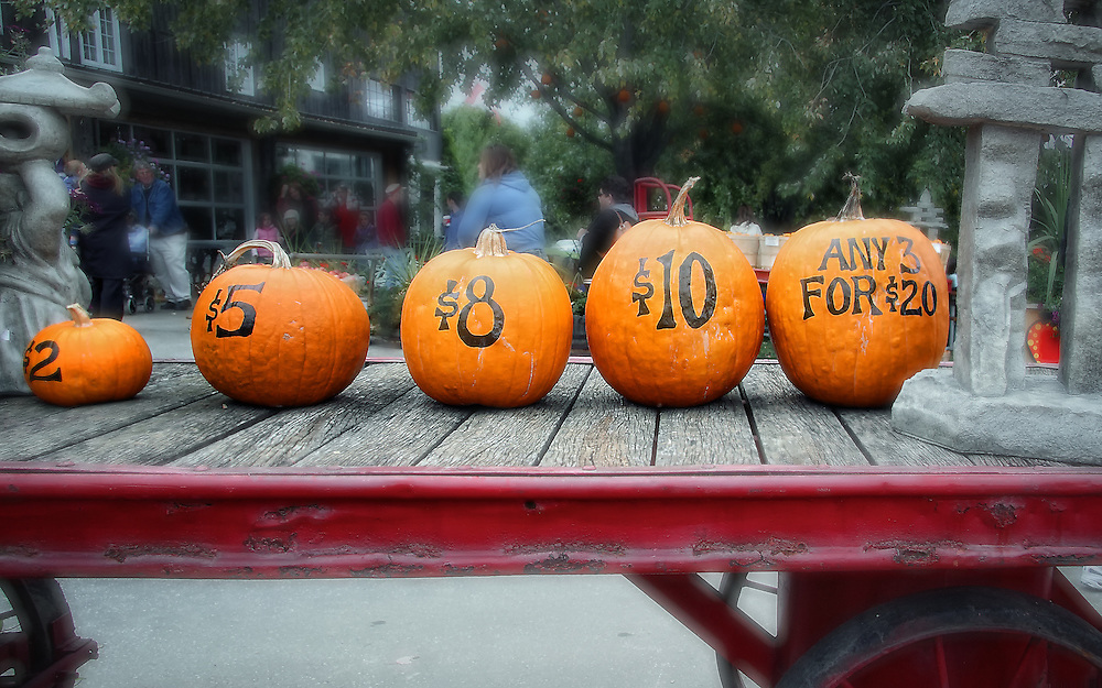 Five different sized pumpkins sit atop a red wagon, priced for sale in celebration of autumn and Hallowe'en.