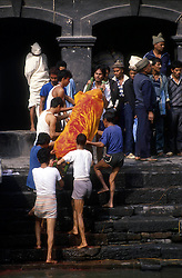 KATHMANDU, NEPAL- The body is carried down to the river and anointed with holy water before being placed on the funeral pyre.  (PHOTO © JOCK FISTICK)