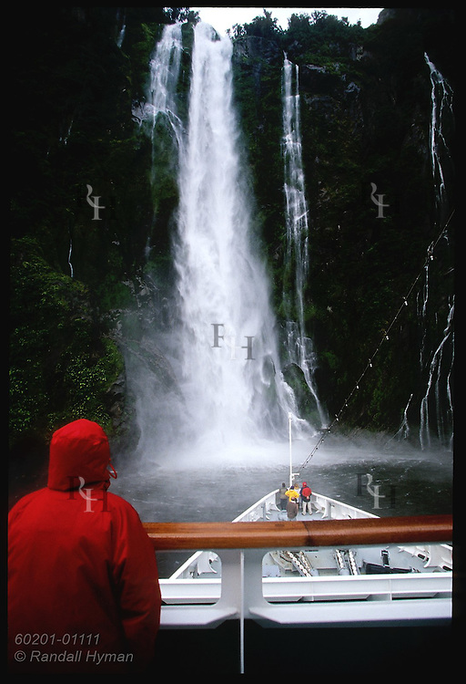 Cruise ship Clipper Odyssey noses up to 530'-high Stirling Falls as man in red watches; Milford Sound, Fiordland NP, NZ