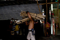 Man carrying bamboo to build scaffolding, Hong Kong.