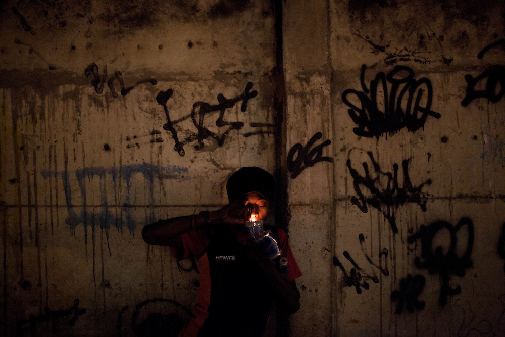 In this Aug. 7, 2012 photo, a man smokes crack in the Manguinhos slum in Rio de Janeiro, Brazil. <br /> <br /> <br />  The South American country began experiencing a public health emergency in recent years as demand for crack boomed and open-air &quot;cracolandias,&quot; or crack lands, popped up in the sprawling urban centers of Rio and Sao Paulo, with hundreds of users gathering to smoke the drug. The federal government announced in early 2012 that more than $2 billion would be spent to fight the epidemic, with the money spent to train local health care workers, purchase thousands of hospital and shelter beds for emergency treatment, and create transitional centers for recovering users.