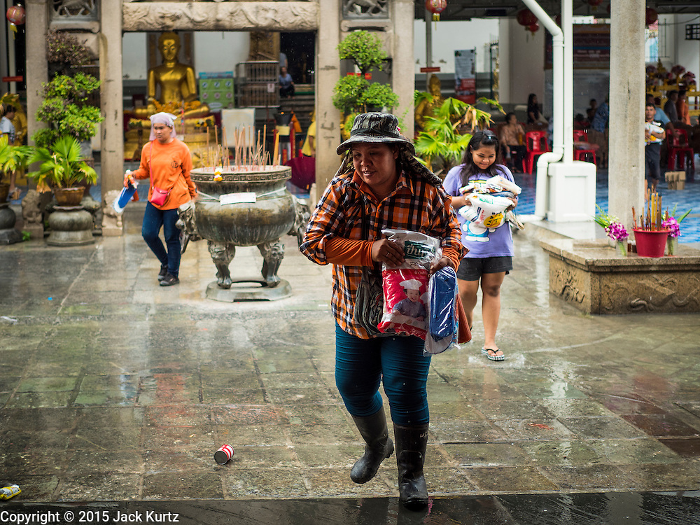 11 SEPTEMBER 2015 - BANGKOK, THAILAND:  People carry away the food they got at a food distribution for poor members of the  Wat Kalayanamit  community in the Thonburi section of Bangkok. Food distribution is a common way of making merit in Chinese Buddhist temples. Wat Kalayanamit, a Thai Theravada temple, was founded by a Chinese-Thai family in the 1820s and observes both Thai and Chinese Buddhist traditions. The food distribution was not related to the temple's efforts to evict people living on the temple grounds, but many of the people at the food distribution live in the houses the temple plans to raze.   PHOTO BY JACK KURTZ