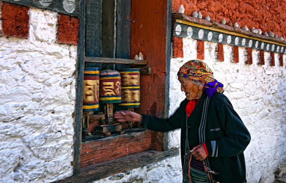 A woman spins the prayer wheels in Bumthang Bhutan.