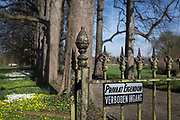 Old wrought iron gates and no entry sign at the entrance of the privately-owned de Merode Castle, out of bounds for locals, on 25th March, in Everberg, Brabant, Belgium. de Merode castle was built in the 16th century and contains three separate buildings: the residence, a building for the animals, a building for employees and the stabling of carriages. Everberg is a town in the Belgian province Flemish-Brabant and is part of the municipality of Kortenberg.