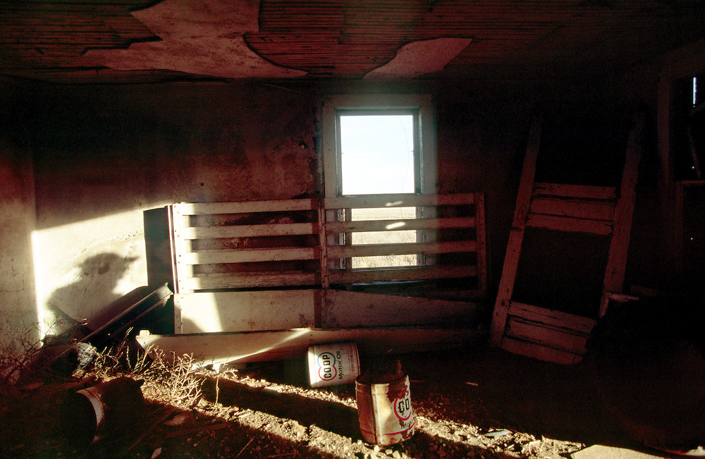 A shadow in the doorway of a vacant farmhouse long ago abandon in eastern Colorado.