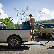 OCTOBER 25 - UTUADO, PUERTO RICO - <br /> Residents drive up to a makeshift station next to the Lago Dos Bocas in Utuado to collect potable water. Troops from Fort Bragg, NC, are using a water filtration system to purify the liquid.<br /> (Photo by Angel Valentin/Freelance)