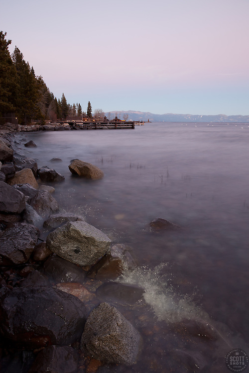 """""""Tahoe Shoreline at Sunset"""" - Photograph of an alpenglow sunset and a wave breaking on rocks along the West Shore of Lake Tahoe."""