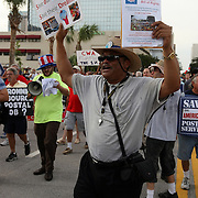 A protester carries signs while walking in a protest parade during the Republican National Convention in Tampa, Fla. on Wednesday, August 29, 2012. (AP Photo/Alex Menendez)