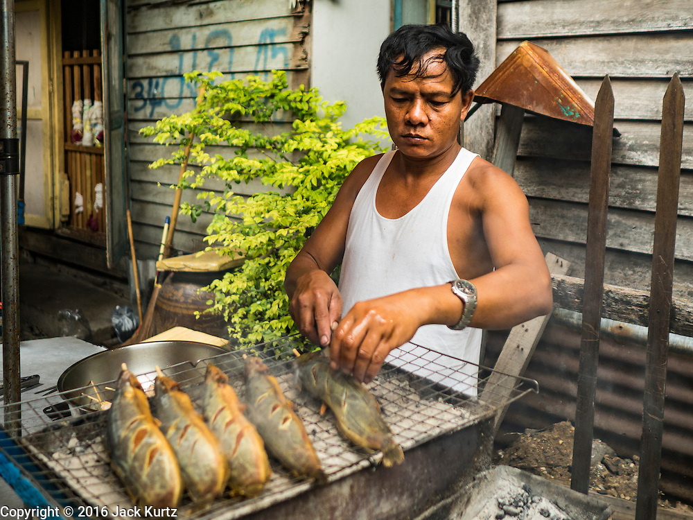 30 JULY 2016 - BANGKOK, THAILAND:  A man who lives in the Pom Mahakan Fort slum grills fish and chicken he sells in the community. Residents of the slum have been told they must leave the fort and that their community will be torn down. Mahakan Fort was built in 1783 during the reign of Siamese King Rama I. It was one of 14 fortresses designed to protect Bangkok from foreign invaders. Only of two are remaining, the others have been torn down. A community developed in the fort when people started building houses and moving into it during the reign of King Rama V (1868-1910). The land was expropriated by Bangkok city government in 1992, but the people living in the fort refused to move. In 2004 courts ruled against the residents and said the city could take the land. Eviction notices have been posted in the community and people given until April 30 to leave, but most residents have refused to move. Residents think Bangkok city officials will start evictions around August 15, but there has not been any official word from the city.     PHOTO BY JACK KURTZ