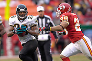 Jacksonville Jaguars running back Fred Taylor (28) rushes up field against pressure from Kansas City safety Sammy Knight (29) in the first half at Arrowhead Stadium in Kansas City, Missouri, December 31, 2006.  The Chiefs beat the Jaguars 35-30.<br />