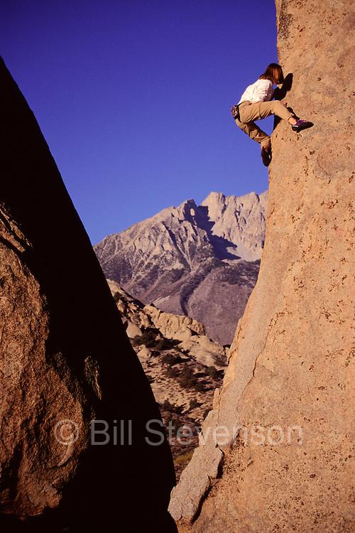 A woman rock climbing in the Buttermilk boulders near Bishop, California.