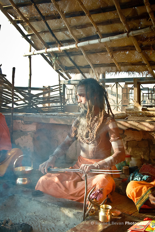 A Hindu holy man playing chimta and chanting at the ghats in Varanasi, Uttar Pradesh, India