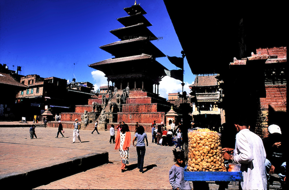 General view of Bhaktapur, one of the seven Monument Zones in the Kathmandu Valley designated by UNESCO, repaired and restored.  Vendor of sweets in the foreground with his cart; visitors and tourists dotted about the pavement; Nayatapola temple across the square.