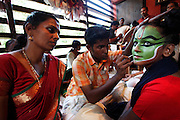 A young female student has her faced made-up for the performance in the back room of the Kuttambalam. Recently renamed the Kalamandalam Deemed University of Arts and Culture but better known by its original name Kerala Kalamandalam it is one of India's most prestigious performing arts schools of which the art of Kathakali is the most renowned discipline. Founded in 1930 by poet and performer Vallathol Narayana Menon and Manakkulam Mukunda Raja who at a time of British Colonial domination feared that the support of local landlords whom held patronage over the arts often employing their own troupes would diminish decided to open the school to guarantee the continuation of the art. 80 years later and with over 500 students and 70 teachers the now turned University of 3 years still trains students in highly stylized classical Indian dance-drama, musical instruments and make-up..Kathakali originated in the present day State of Kerala around the 17th century and whilst having been adapted and modernised throughout history remains an intricate part of Keralan culture in telling ancient Hindu epics. In the local dialect of Malayalam, the word 'Katha' means story and 'Kali' means play.
