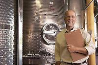 Portrait of winemaker standing next to wine vat holding clipboard