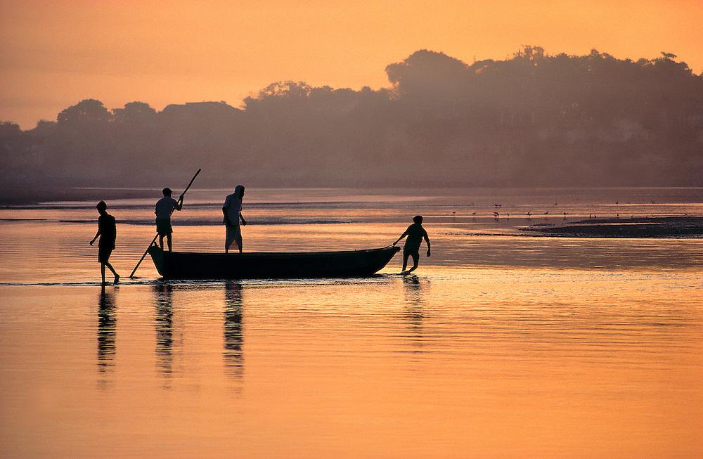 Men pull their boat across the shallow Jumna River at sunrise, near the Taj Mahal in Agra, India.