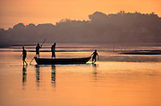 Men pull their boat across the shallow Jumna River at sunrise, near the Taj Mahal in Agra, India.